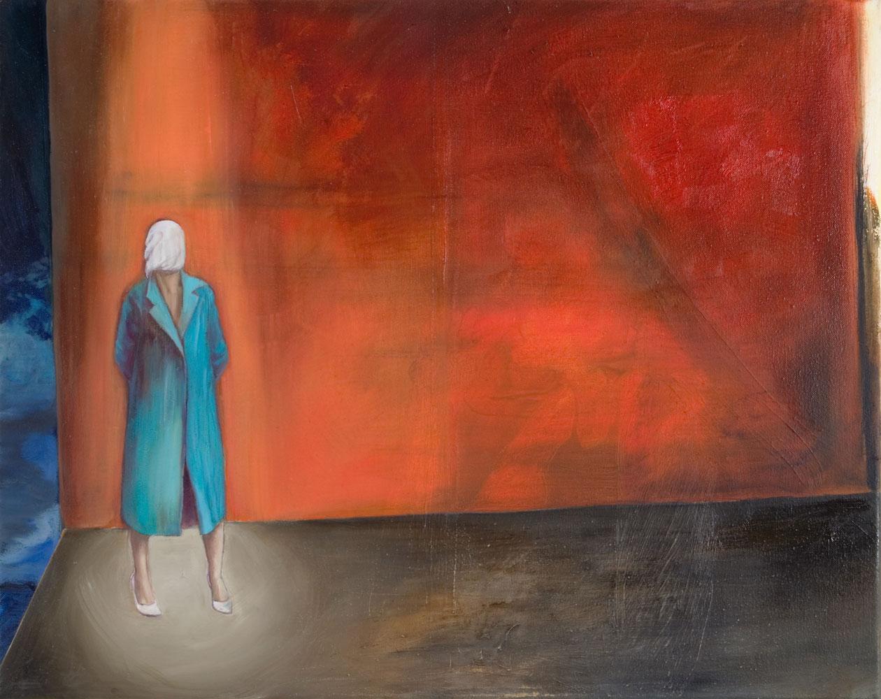 eine Frau im blauen Mantel und weißen Tuch vorm Gesicht steht vor orangeroter Wand, ein Spot auf ihr