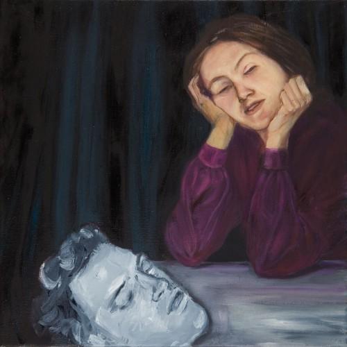 Frau mit geschlossenen Augen am Tisch, vor ihr liegt ein grauer männlicher Kopf