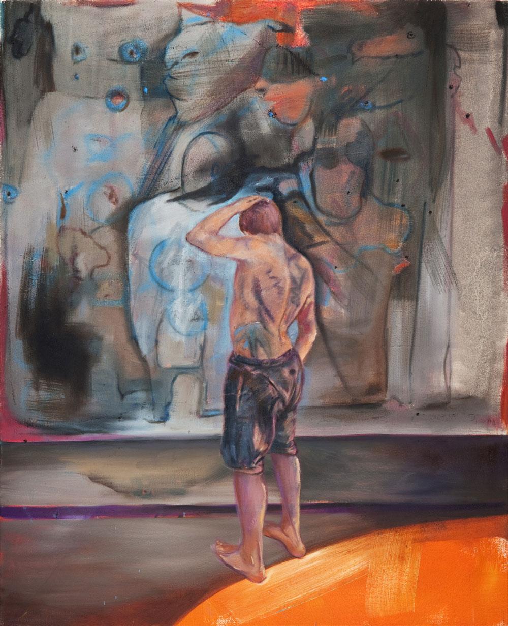 Mann mit nacktem tätowierten Oberkörper steht vor bemalter Wand und hält sich den Kopf